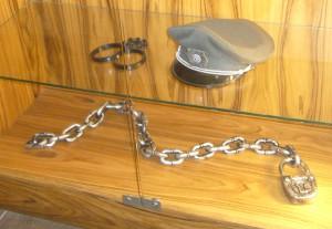 Entraves et casquette de surveillant dans les vitrines de l'hôtel. Photographie de Réjane Boursier