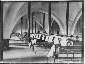 Un des dortoirs communs aménagés dans l'abbatiale, vers 1890, © Archives départementales de Maine et Loire, fonds Célestin Port.